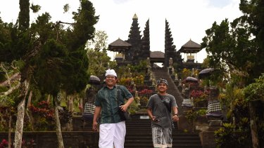 Pande Togi (left) and Komang Irvan (right) come down the steps after praying at the Besakih Mother Temple inside the 9km danger zone despite Mount Agung threatening to erupt. The Besakih Mother Temple is a famous Balinese tourist spot attracting hundreds of tourists a day. Tourists are staying away as Mount Agung threatens to erupt. Bali, Indonesia.