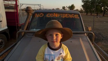 On the road … Harrison Phillips, on the bonnet of his father's ute, joins the protest at Katherine yesterday.