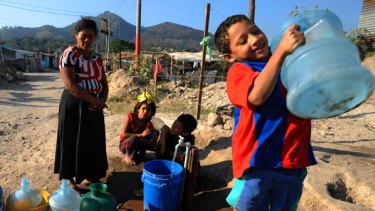 People wait to fill up bottles of water at a settlement in San Salvador.