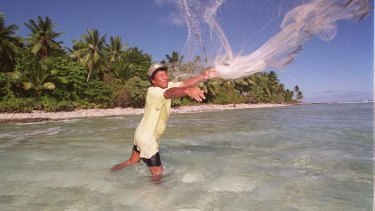 Rising tide: A fisherman throws out his net on the shores of Majuro, Marshall Islands, which is at threat of sea level rises.