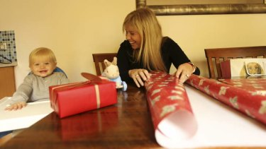 Cheques and balances: Emily Lamb, with son Rufus, wrap Christmas gifts for friends and family in Britain: