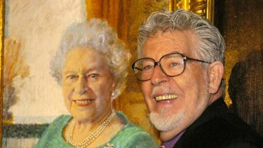 Rolf Harris poses beside his portrait of Queen Elizabeth II at Buckingham Palace in December, 2005.