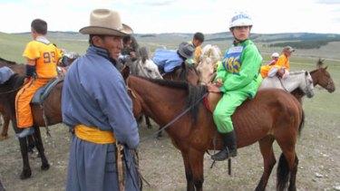 Lining up...Angus Paradice, with horse trainer Ulzil Byambajudger, gets ready to compete in the traditional horse races at the Nadaam festival in Mongolia.