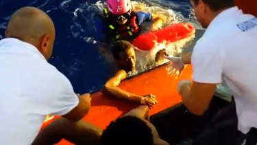 This scene from a video shows rescuers helping a survivor of the capsized immigrant boat to safety off the Italian island of Lampedusa.