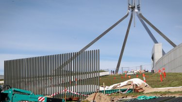 A security fence is installed across the lawns of Parliament House in Canberra.