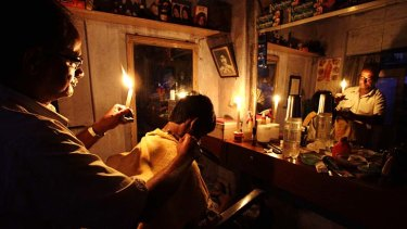 Trying to keep a cut above … a barber holds a candle while giving a haircut to a customer in Kolkata, India, during the world's biggest blackout which left 600 million people without power for hours.