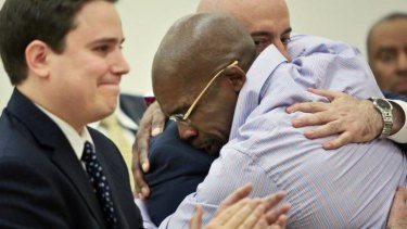 Jonathan Fleming hugs his attorney Anthony Mayol while his other attorney Taylor Koss applauds in Brooklyn's Supreme court, after a judge declared him a free man.
