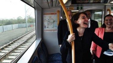 Light moment on new heavy rail: Transport Minister Gladys Berejiklian enjoys the journey.