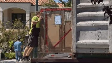 Removalists pack up the Oswals' belongings at their Dalkeith mansion this morning.