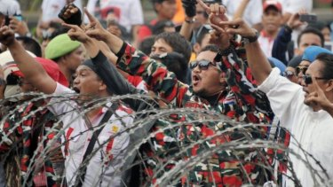 Chanting and singing: Presidential candidate Prabowo Subianto's  supporters try to pass a police blockade near the Constitutional Court in Jakarta on Thursday.