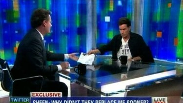 A screen image of Charlie Sheen passing Piers Morgan a document showing how he has been drug free.
