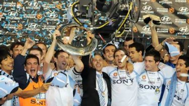 Time to party ... Sydney FC players, including injured skipper Steve Corica, hold aloft the A-League trophy for the second time after claiming the inaugural title