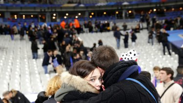 A supporter comforts a friend at the Stade de France.
