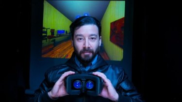 Virtual reality designer Oscar Raby with an Oculus Rift prototype headset, and, behind, his Assent experience.