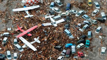 Cars and airplanes are left destroyed by the tsunami.