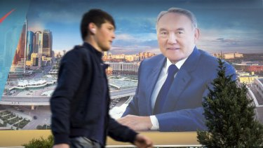 A man walks past an election banner of Kazakhstan's President and presidential candidate Nursultan Nazarbayev on Monday.