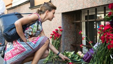 A woman lays flowers in front of the Spanish embassy in Moscow, Russia for the victims of a terrorist attack in Spain.