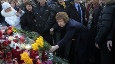 New white knight: EU foreign policy chief Catherine Ashton places flowers at a memorial for the people killed in clashes with the police in central Kiev, Ukraine.