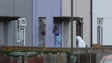 Forensic officers enter the home in southwest London for clues, following the arrest on an 18-year-old man on Saturday.