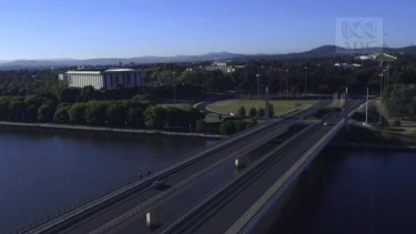 The opening shot of Canberra in Episode 1 of The Code: an aerial view of a car crossing Commonwealth Avenue bridge towards Parliament House.