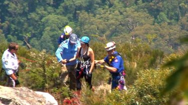 The young woman involved in the abseiling accident is led from the bush by rescuers.