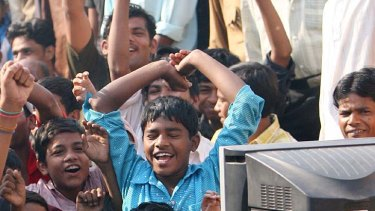 Indian children watch television in Mumbai, which receives the Australia Network broadcasts.