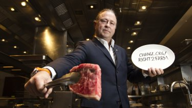 Chef Neil Perry with a raw Blackmore wagyu steak at Rockpool.