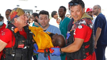 Turkish doctors transport a critically wounded man on stretcher into a waiting Turkish air ambulance.