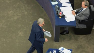 Jean-Claude Juncker, returning to his seat after speaking, walks past former UK Independence Party leader Nigel Farage, a member of the European Parliament and champion of Brexit.