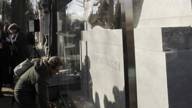 Loved to death ... Oscar Wilde's tomb in Paris has been restored to its former glory, with an added barrier to stop fans from kissing it.