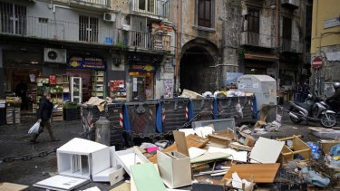 Garbage strewn around trash cans outside a store in Naples, Italy.