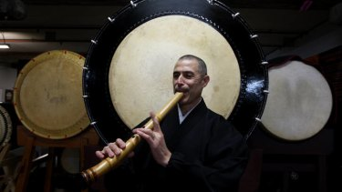 Dr Riley Lee plays the shakuhachi in front of taiko drums.