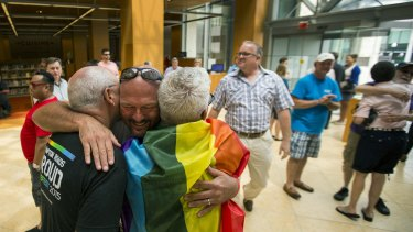 Eric Hause of Norfolk, centre, hugs Claus Ihlemann and Robert Roman in the lobby of the Slover Library Friday morning, in Norfolk, Virginia.