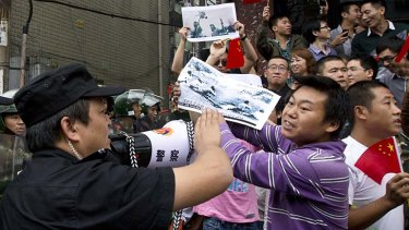 Textbook copy ... protesters in Chengdu last week hold a photograph depicting cruelty suffered by Chinese under Japanese occupation last century.