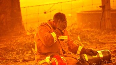 An unidentified firefighter is overcome by exhaustion at Bunyip State Park.