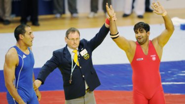 The decision ... India's Anil Kumar is awarded the gold medal, as Australia's Hassene Fkiri looks on.