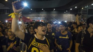 Student protesters shine lights from their phones as they chant pro-democracy slogans on the streets of Hong Kong.