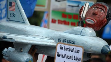 A protester holds a replica of a US jet fighter near the US embassy in Manila to denounce the decision to militarily intervene in Libya.
