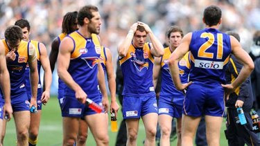 West Coast players trudge off the MCG after their loss.
