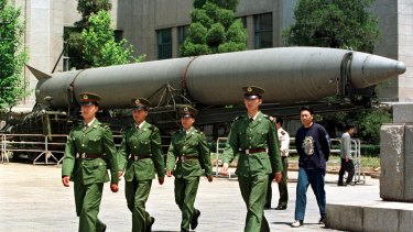 Chinese soldiers march past a missile on display at Beijing's Military Museum.