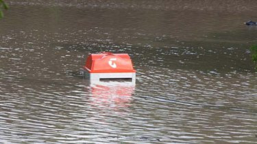 Submerged ...a Telstra phone booth under floodwater in Fairfield in southern Brisbane.
