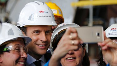 French President Emmanuel Macron poses for selfies as he visits the MSC Meraviglia cruise ship at the STX shipyard site in Saint-Nazaire, western France.