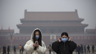 Residents wear masks to protect against pollution in Tiananmen Square.