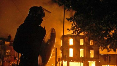 Burning down ... a riot police officer watches as a building burns in Croydon.