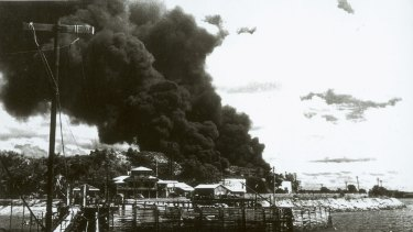 Darwin, 19 February 1942. People at Government House look at the smoke billowing from ships ablaze in the harbour after the first Japanese air raids.