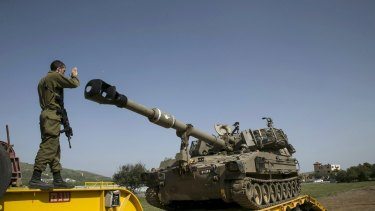 An Israeli soldier directs a mobile artillery unit in the Druze village of Buqata in the Golan Heights on Monday.