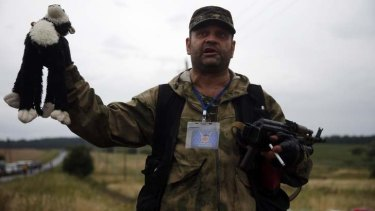 A pro-Russian separatist holds up a stuffed toy found at the crash site.
