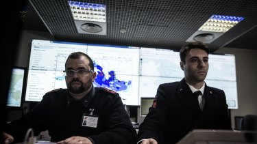 Italian coast guard officers use monitors to track ships navigating the area where the boat believed to be crowded with perhaps as many as 700 migrants capsized in the waters north of Libya.