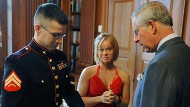 Todd Nicely, left, shows his prosthetic hand to Prince Charles as his wife Heather looks on.