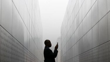 "Todd McCormick takes a photograph of names on the walls of the newly constructed ""Empty Sky Memorial"" at Liberty State Park in New Jersey."